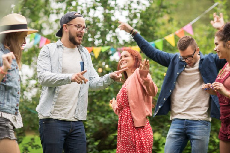 friends dancing and having a great time at backyard party.